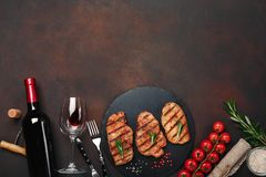 Grilled pork steaks on stone with bottle of wine, wine glass, knife and fork on rusty background stock image