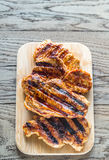 Grilled pork steaks on the wooden board Stock Photos