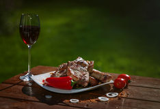 Grilled pork steaks on a wooden table with a glass of wine Royalty Free Stock Image