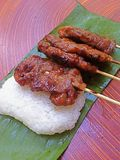 Grilled pork stick and sticky rice with green container, banana leaf Royalty Free Stock Images