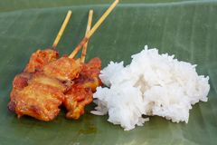 Grilled pork with sticky rice on banana leaf background. royalty free stock photography