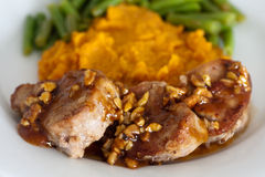 Grilled pork tenderloin medallions. Served with mashed sweet potatoes, green beans and pecan nuts with honey Royalty Free Stock Photography