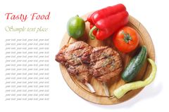 Grilled pork and vegetables on a cutting board isolated top view Stock Images