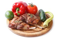 Grilled pork and vegetables on a cutting board isolated on white Royalty Free Stock Image