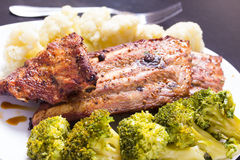 Grilled pork with vegetables. Grilled pork ribs meat with cooked cauliflower and broccoli on the withe plate Stock Images