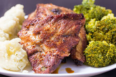 Grilled pork with vegetables. Grilled pork ribs meat with cooked cauliflower and broccoli on the withe plate Royalty Free Stock Photos