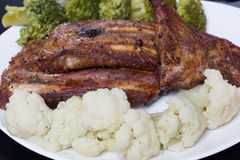 Grilled pork with vegetables. Grilled pork ribs meat with cooked cauliflower and broccoli on the withe plate Stock Photos