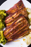 Grilled pork with vegetables. Grilled pork ribs meat with cooked cauliflower and broccoli on the withe plate Stock Photography