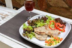 Grilled pork on white plate with glass of wine Royalty Free Stock Photos