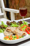 Grilled pork on white plate with glass of wine Stock Images