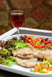 Grilled pork on white plate with glass of wine Royalty Free Stock Photo