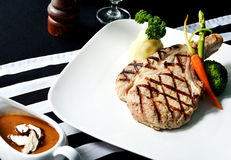 Grilled Porkchop Steak on the dining table Royalty Free Stock Photography