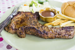 Grilled porkchop. With vegetable, bun and french fries Stock Photos