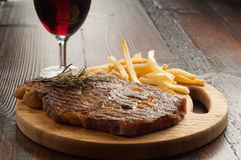 Grilled porterhouse with french fry. And glass of red wine Royalty Free Stock Photo