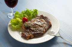 Grilled porterhouse with salad. And glass of red wine Royalty Free Stock Image