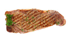 Grilled Porterhouse Steak. Grilled porterhouse beef steak, isolated on white.  Garnished with parsley and ground black pepper Stock Photo