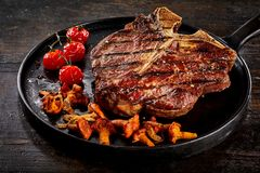 Grilled porterhouse steak with chanterelles Royalty Free Stock Photography