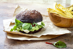 Grilled portobello bun mushroom burger. Vegan, gluten free, grain free, healthy veggies hamburger with guacamole, fresh vegetables. Cashew cheese sauce and royalty free stock photos