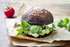Grilled portobello bun mushroom burger. Vegan, gluten free, grain free, healthy veggies hamburger with guacamole, fresh vegetables. And cashew cheese sauce royalty free stock photography
