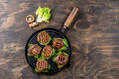 Grilled portobello bun mushroom burgers on cast iron grill pan ob wooden background, top view.  royalty free stock photo
