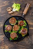 Grilled portobello bun mushroom burgers on cast iron grill pan ob wooden background, top view.  royalty free stock photography