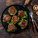 Grilled portobello bun mushroom burgers on cast iron grill pan ob wooden background, top view.  royalty free stock photos