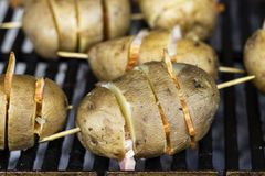 Grilled potato with bacon. Baked potatoes with lard skewered on grilled skewers Stock Photo