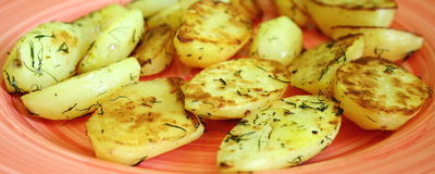Grilled potatoes. Some grilled potatoes with orange background stock photography