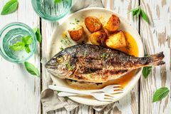Grilled potatoes and seabream with cherry tomatoes and thyme. On old table royalty free stock photos