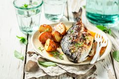 Grilled potatoes and seabream with herbs and tomatoes. On old table stock images