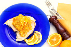 Grilled poulet fillet with oranges sauce over blue plate and vin Stock Photo