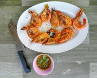 Grilled prawn on white dish, knife and seafood sauce on the tabl stock images