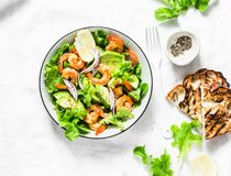 Grilled prawns, avocado, garden herbs salad - delicious healthy snack, appetizers, tapas on a light background, top view royalty free stock photography