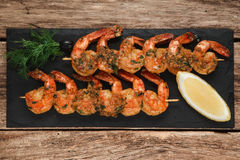 Grilled prawns on black slate. Mediterranean food. Japanese cuisine. Fried shrimps served on black slate with herbs and lemon, top view. Restaurant menu photo Royalty Free Stock Photo