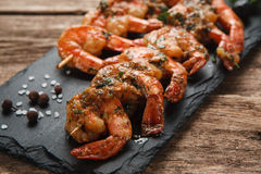 Grilled prawns on black slate. Mediterranean food. Japanese seafood. Fried spicy shrimps with herbs on wooden skewers served on black slate, close up view Royalty Free Stock Photo
