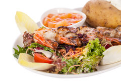Grilled prawns with endive salad and jacket potato Royalty Free Stock Images