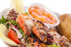 Grilled prawns with endive salad and jacket potato Stock Photography