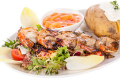 Grilled prawns with endive salad and jacket potato Royalty Free Stock Photo