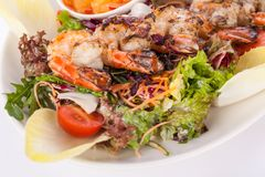 Grilled prawns with endive salad and jacket potato Royalty Free Stock Image