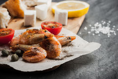 Grilled prawns on the peace of paper with tomatoes,  cheese and bread on the wooden board Stock Photo