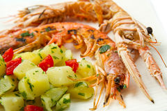 Grilled prawns with potatoes Royalty Free Stock Images