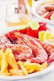 Grilled prawns with a side of fries and fresh veggies Stock Photos