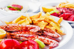 Grilled prawns with a side of fries and fresh veggies Stock Image