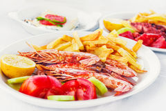 Grilled prawns with a side of fries and fresh veggies Royalty Free Stock Photos