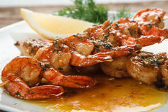Grilled prawns on white plate. Mediterranean food. Tasty Japanese seafood. Fried spicy shrimps on wooden skewers served on plate with herbs and lemon, close up Stock Photography