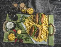 Grilled pulled beef sandwich, burger, french fries, sauce, dark beer, corn on a wooden tray