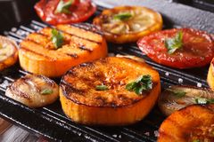 Grilled pumpkin and vegetables on grill pan. Horizontal macro Stock Image
