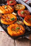 Grilled pumpkin and vegetables on grill pan. Vertical macro Royalty Free Stock Photo