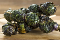 Grilled Purple Brussels Sprouts Kabobson Skewers. Three grilled organic purple Brussels sprouts on skewers set on wood Stock Photo