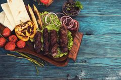 Grilled quail meat. With vegetable on a blue wooden background Royalty Free Stock Photos